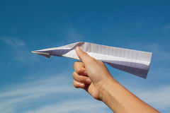 Hand with paper plane against blue sky Stock Image