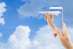 Hand with paper plane with mobile phone against blue sky sending email. Communication concept royalty free stock images