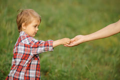 Hand of parent and child portrait. Child give his parent something on the nature Stock Images