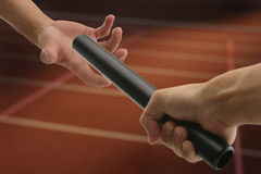 Hand passing baton. Hand passing a baton to another party royalty free stock photography