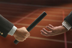 Hand passing baton. Hand passing a baton to another party royalty free stock images