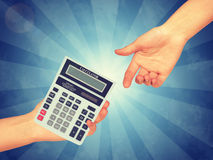 Hand passing a calculator stock images