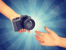 Hand passing camera royalty free stock photography