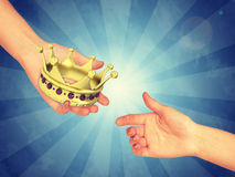 Hand passing gold crown Royalty Free Stock Photo