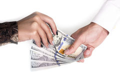 Hand passing money. Man's hand passes a female hand hundred-dollar bills isolated on white background Royalty Free Stock Images