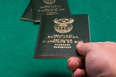Hand passing South African passport stock photography