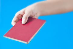 Hand with passport. Isolated on blue background (landscape orientation Stock Image