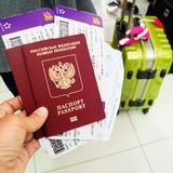 Hand with passports and plane tickets against the backdrop of su Royalty Free Stock Photo