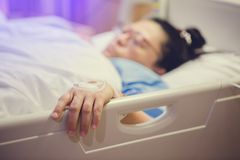 Hand of patient draw to Infusion pumps and saline bag stock images