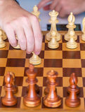 Hand with pawn makes first move on chess Board Royalty Free Stock Photos