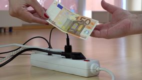 Hand pay euro banknote for high electricity usage in front of switch with plugs. Modern time high energy needs concept stock video