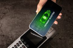 Hand paying with bitcoin. Hand paying with digital currency from smartphonen stock photos