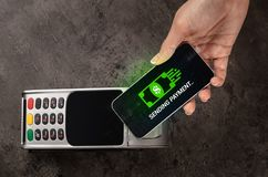 Hand paying with bitcoin. Hand paying with digital currency from smartphonen stock image