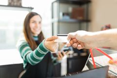 Hand Paying Through Credit Card In Bread Store. Cropped image of customer giving credit card to cashier in bakery stock photography