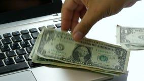 Hand paying dollars us banknotes laptop keyboard. Hand paying dollars us or usa banknotes laptop keyboard n stock video footage