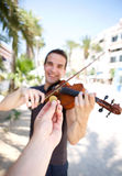 Hand paying money to busker man playing violin. Outside Royalty Free Stock Image