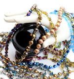 Hand with pearls, beads and crystal ball. White display hand over black crystal glass ball on stand, surrounded by many crystal and pearl necklaces Stock Photo