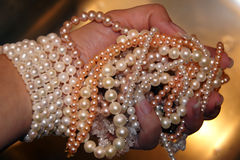 Hand with pearls. Bunch of pearls necklace in womens hand Stock Images
