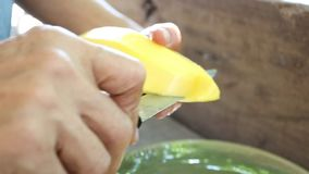 Hand peeling ripe mango in Thai style. stock footage