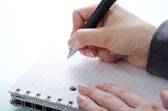 Hand with a pen. Woman's hand with a pen on a notebook royalty free stock photography