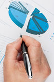 Hand with pen. Business analyst working - hand with pen, sheet and graph stock image