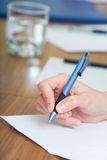 Hand with pen. Image of female hand holding the pen over the paper Royalty Free Stock Images