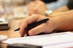Hand with pen. At business meeting - close up stock photography