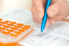 Hand with Pen Analyses Figures by a calculator Stock Photography