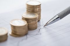 Hand with pen analyzing line and coin graphs on desk Royalty Free Stock Photo
