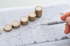 Hand with pen analyzing line and coin graphs on desk Royalty Free Stock Photos