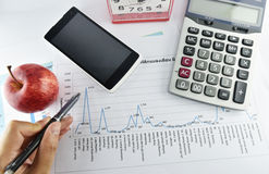 Hand, pen, apple, money,clock, telephone and calculator placed o Stock Photos