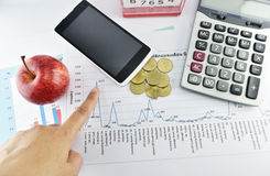 Hand, pen, apple, money,clock, telephone and calculator placed o Royalty Free Stock Photography