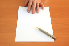 Hand, pen and blank document. Male hand presents a blank document and a pen Stock Photo