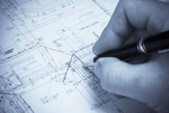 Hand with pen on a blueprint Royalty Free Stock Photography