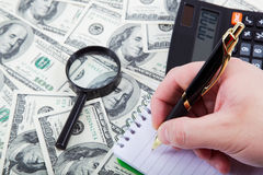 Hand with pen and calculator on a background of money. Business Stock Image
