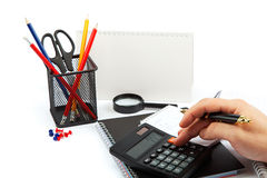 Hand with pen, calculator, notepad and office supplies. Stock Photo
