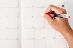 Hand with pen on calendar page. Stock Photo