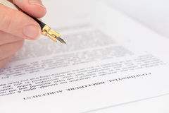 Hand with Pen Checking Disclosure Agreement. Hand holding fountain pen over disclosure agreement Stock Photos