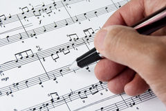 A Hand With Pen Checking Musical Notes Royalty Free Stock Image