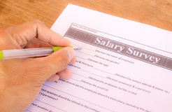 Hand with pen choosing salary survey from Royalty Free Stock Images