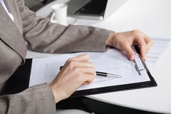 Hand with pen and clipboard. Hand of a businesswoman at her desk with a pen and a clipboard Royalty Free Stock Image