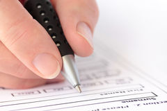 Hand with Pen Completing Form Closeup Royalty Free Stock Photos