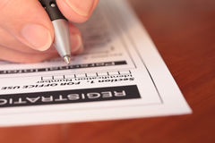 Hand with Pen Completing Form On Table Closeup Stock Image