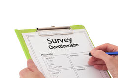 Hand with Pen Completing Market Research Survey Qu