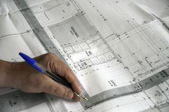 Hand with pen on construction plans. Close up of a male hand with a blue pen resting on a construction plan royalty free stock photo