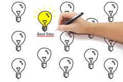 Hand with pen drawing yellow light bulb with good idea word amon. G many on pure white background Royalty Free Stock Images