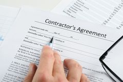 Hand With Pen And Eyeglasses Over Agreement. Close-up Of Hand With Pen And Eyeglasses Over Contractor Agreement Stock Photography