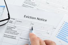 Hand with pen and eyeglasses over eviction notice. Close-up Of Hand With Pen And Eyeglasses Over Eviction Notice Paper royalty free stock photos