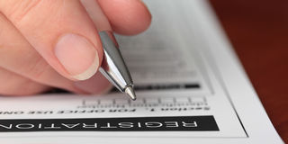 Hand with Pen Filling out a Form Closeup Royalty Free Stock Photography