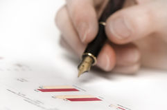 Hand with pen and graphics. Close up of a hand holding a pen. sharpness on graphics Stock Image
